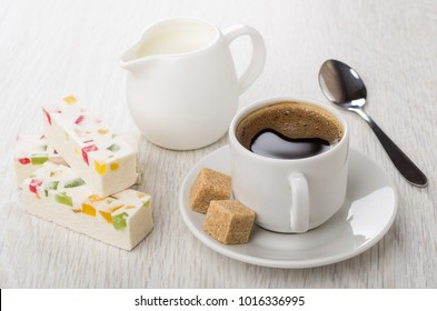 Marshmallow with marmalade, jug of milk, coffee in cup and sugar, spoon on wooden table