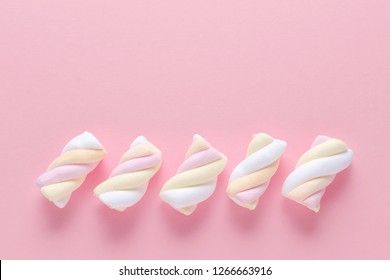 marshmallow in pastel colors on pink background with copy space