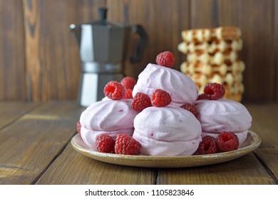 Marshmallow with raspberries on a wooden background