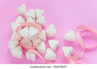 Marshmallows in heart shapes for Valentines day over pink paper background and ribbon to celebrate sweet love candy for couples, selective focus