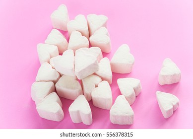 Marshmallows in heart shapes for Valentines day over pink paper background to celebrate sweet love candy for couples, selective focus