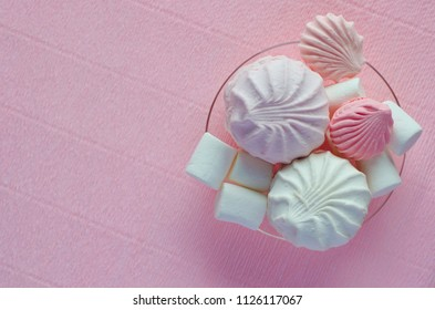 Marshmallows, meringues on the transparent plate on the pink background.Isolated.Top view.Minimalism.