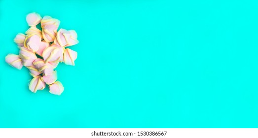 Marshmallows on blue background with copyspace, top view. Background of colorful mini marshmallows, pastel color dessert, sweet food Winter food background concept.
