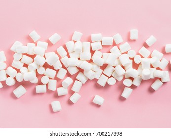 Marshmallows on pink background with copyspace. Flat lay or top view. Background or texture of colorful mini marshmallows. Winter food background concept.