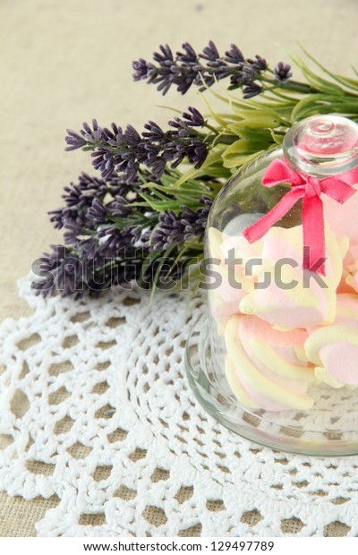 Marshmallows on saucer with transparent cover on light background