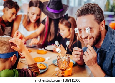 Marshmallows on sticks. Smiling bearded father holding marshmallows on sticks while celebrating Halloween with wife and children