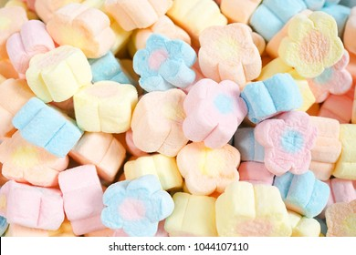 Marshmallows. A pile of cute flower marshmallow, colorful food pattern. Can be used for food container advertising. Selective focus on the orange and blue flowers in the middle.