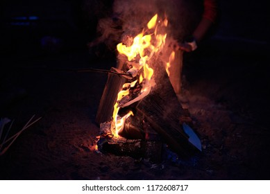 Marshmallows toasting on a stick over a campfire late at night