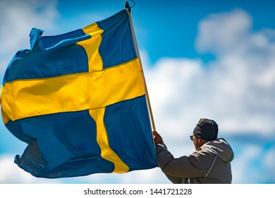 MARSTRAND, SWEDEN - JULI 3, 2019: GKSS Match Cup Sweden - Man Holding Flag in Hard wind - Whole Swedish Flag in wind hold by man with Blue Sky Background.