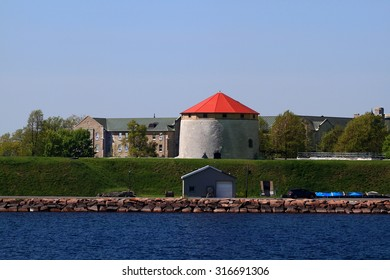 Martello Tower on the Frederick Point with Royal Military Collage of Canada main building on background. Fort Frederick National Historic Site view from St. Lawrence River