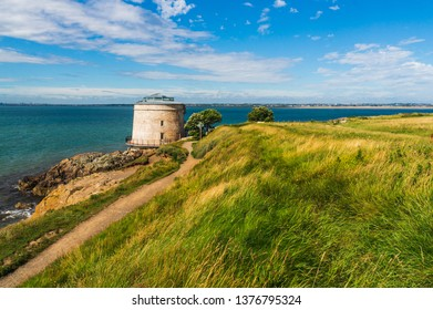Martello tower, a small defensive fort in a landscape of green grass swaying in the wind and creating wave like patterns. Irish seaside in Sutton, County Dublin, Ireland.