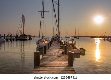 Martha's Vineyard, MA / United States-May 29, 2016: Sail boat and motorboat tied up to a dock at sunrise.