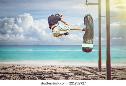 martial artist in action. performing a flying kick on a boxing bag on the beach. idyllic atmosphere