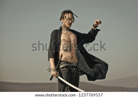 f2956604a Warrior with dreadlocks and open clothes showing tattooed torso.  Concentration and