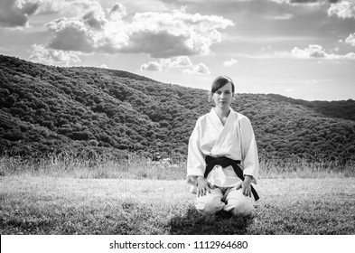Martial arts. Female athlete doing karate exercise in nature. Grayscale image.