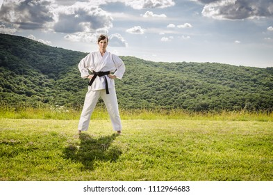 Martial arts. Female athlete doing karate exercise in nature