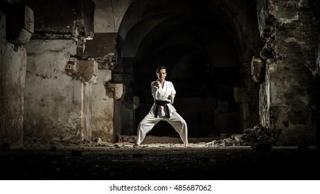 Martial arts. Female athlete doing karate exercise in dark grunge building.