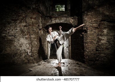 Martial arts. Girl exercising karate against old grunge wall. High kick.