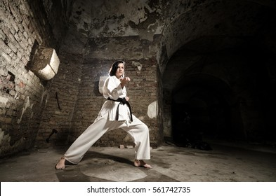 Martial arts. Girl exercising karate against old grunge wall.
