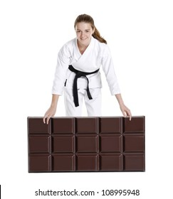 Martial arts girl holding a big chocolate bar.karate girl portrait.Martial arts and karate kid portrait.