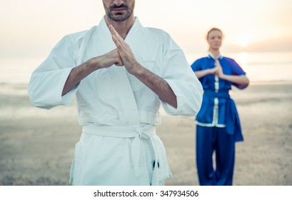 Martial arts greetings. Couple training on the beach in the morning