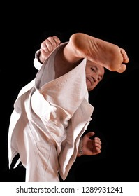 Martial arts karate master training on black background.