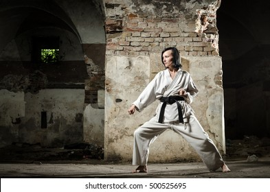Martial arts. Young female athlete exercising karate, old grunge wall background.