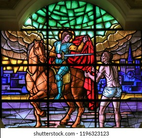 Martina Franca, Italy - March 15, 2015: Stained glass depicting Saint Martin cutting a part of his cloak and handing it over to a beggar, in the Basilica of San Martino in Martina Franca, Italy.