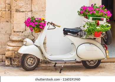 Martina Franca, Puglia, Italy - 05/31/2018 - A decorative Vespa scooter with flowers in front of a store in the old town
