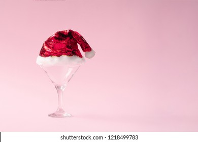 Martini or champagne glass with santas hat on pink background with copy space. Minimal flat lay Christmas theme. New year party concept.