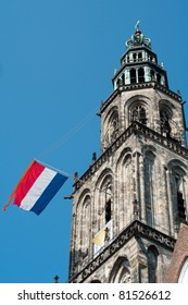 Martini church tower with Dutch flag and blue sky. Shot during queensday