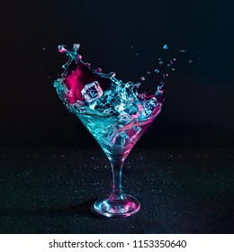 Martini cocktail drink splash with ice cubes in neon iridescent pink and blue colors. Minimal night party life concept.