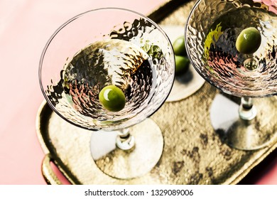 Martini cocktail with green olive on gold-colored tray