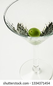 Martini cocktail with green olive on white background