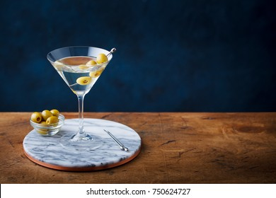 Martini cocktail with green olives on marble cutting board. Copy space.
