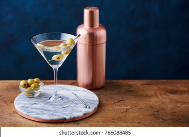 Martini cocktail with green olives, shaker on marble board, wooden table. Copy space.