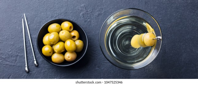 Martini cocktail with green olives. Slate background. Top view.