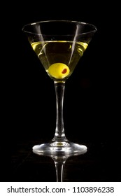 Martini cocktail with olives on a black background