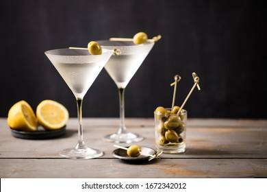 Martini cocktail on wooden worktop. Olive garnish. Space for text