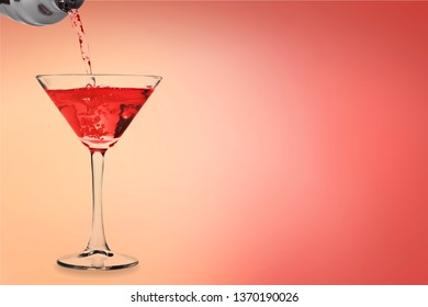 Martini cocktail poured from shaker into glass isolated on white