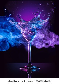 martini cocktail splashing on blue and purple smoky background