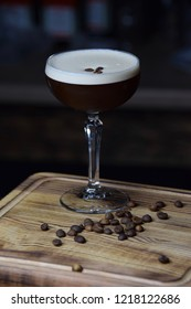 Martini espresso cocktail on a wooden desk served with fried coffee seeds in front of black background. Cocktails with cofee