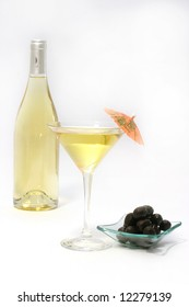 Martini glass with black olives and bottle