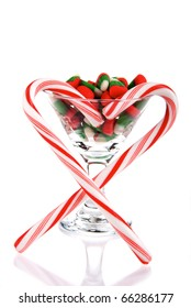 Martini Glass with christmas and new year candies, heart of candy canes isolated on a white background