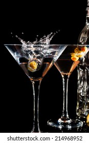 Martini glass with olive on black background