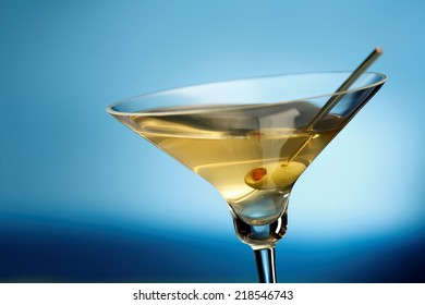 Martini glass with olive, sea on the background