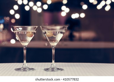 Martini glasses on a bar.