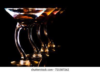 Martini Glasses in a row with a dark background with copy space.