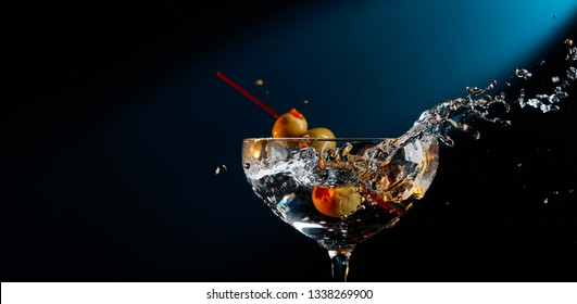 Martini with green olives. Cocktail in glass with splashes.  Copy space for your text.