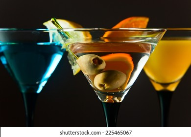 martini with green olives , focus on a berryes